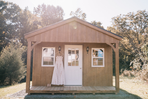 bridal gown hanging in front of rustic cabin at elegant northern virginia farm venue