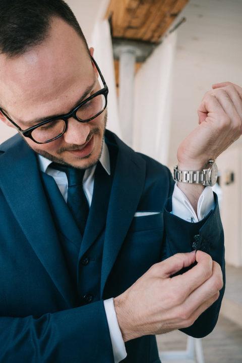 groom in dark blue suit prepares for his wedding at 48 Fields barn venue in Northern Virginia