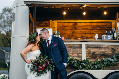 Bride and groom pose in front of mobile wedding bar