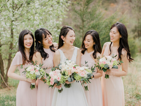 Bride and bridesmaids hold bouquets